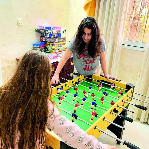 דן ואחותה, ליד שולחן הכדורגל. מעבירות את הזמן גם עם משחקים של פעם