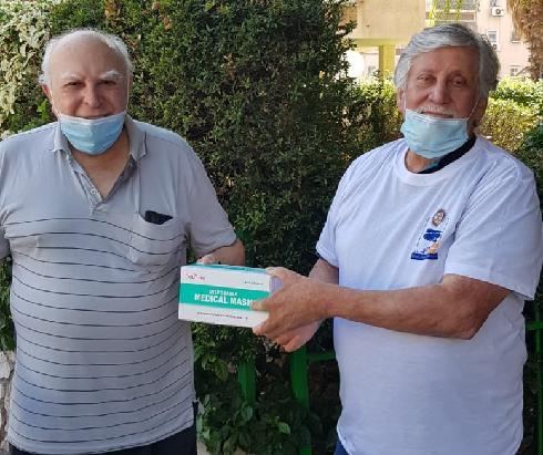 מתנדב רוטרי ויקיר העיר נתן שרפמן (מימין) מעניק חבילת מסכות ליקיר העיר ניסן שאלתיאל