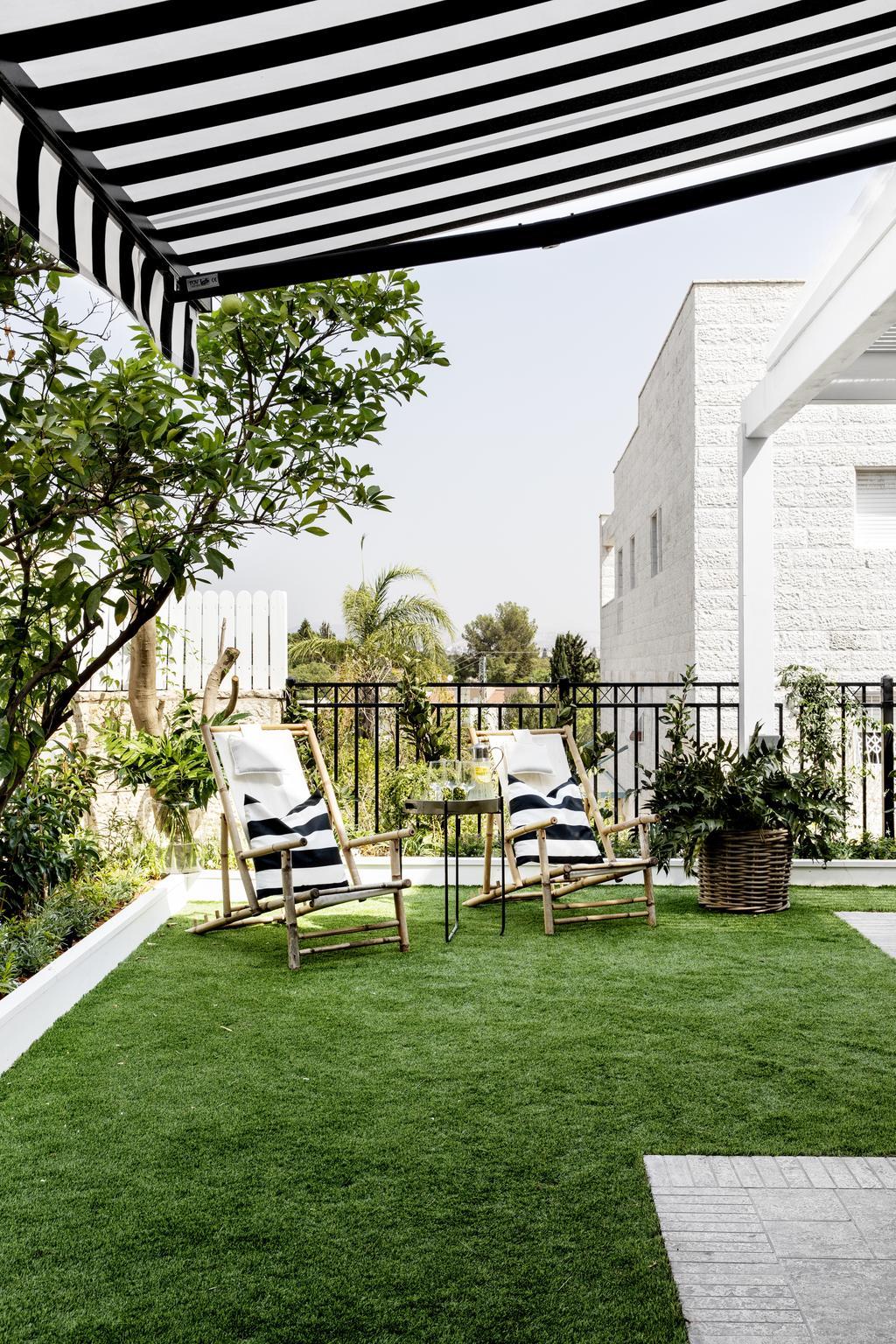 דשא וצמחייה רעננה ממסגרים את הגינה הלא גדולה של הבית. צילום: איתי בנית